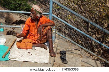 KEESRAGUTTA,HYDERABAD,INDIA-FEBRUARY 24:Indian Hindu senior man seeks help or alms or begs on stairs of temple during Mahasivaratri festival on Frbruary 24,2017 in keesaragutta,Hyderabad,India.