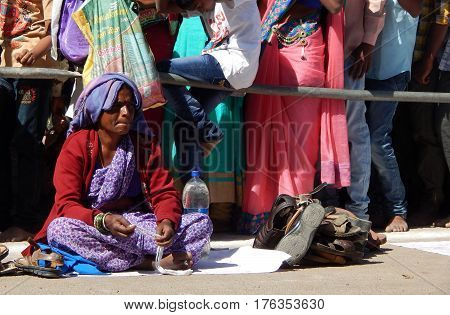 KEESARAGUTTA,HYDERABAD,INDIA;FEBRUARY 24:Woman keeps watch on footwear of people in queue visiting temple on Mahasivaratri on February 24,2017 in Hyderabad,India