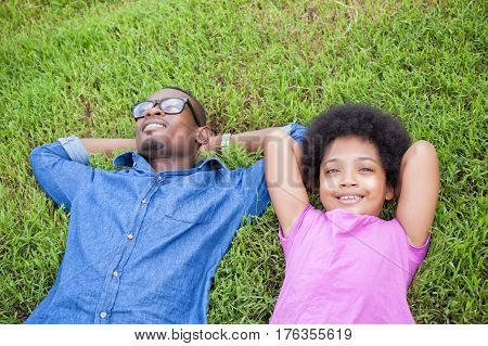 African American Young Man And Little Kid Relaxing And Looking At Clouds On Green Park