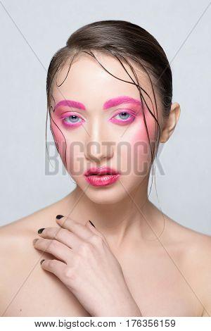 Woman with creative  pink colorful make-up. Beautiful brunette girl with pink brows and lashes glossy lips wet hair
