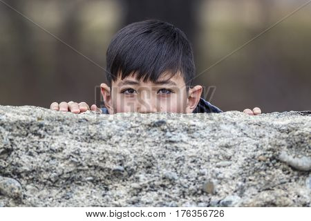 A playful boy peeks out from behind an old stone wall.