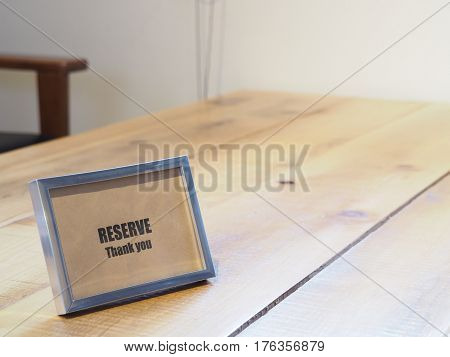 Reserved sign on wooden table in restaurant.