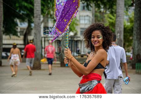 RIO DE JANEIRO, BRAZIL - FEBRUARY 28, 2017: Beautiful smiling woman with curly hair and nose piercing, holding purple flag at Bloco Orquestra Voadora, Carnaval 2017