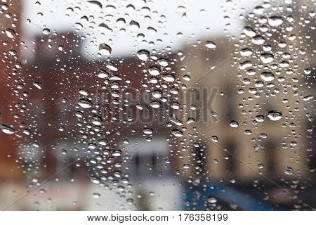 shallow focus on rain covered window with unfocused city buildings in the background