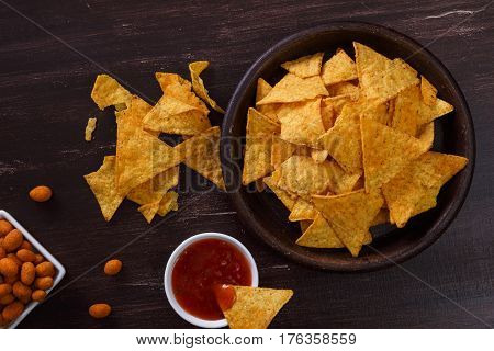 Nachos chips. Tortilla snack with sweet salsa or chilli sauce. Mexican salsa nuts. Rustic plate on wooden background.