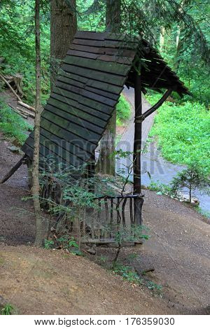 Old wooden canopy with bench in forest park