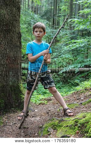 Boy with long wooden stick in forest park