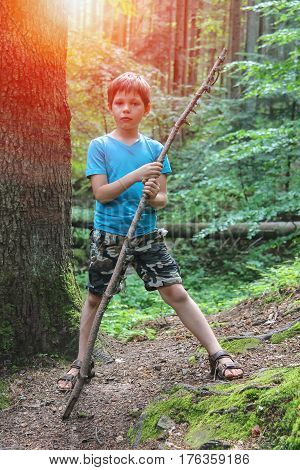 Boy with long wooden stick in forest park in sunlight