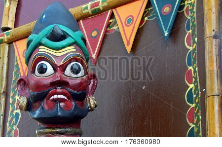HYDERABAD,INDIA-FEBRUARY 27:Closeup of a Indian tribal man head wooden carving with flags and decorative art background on February 27,2017 in Hyderabad,India