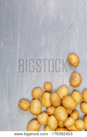 Potatoes lying on wooden table. Raw new potato. Fresh natural food. Organic vegetables on wooden background.
