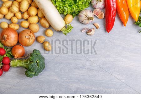 Fresh vegetables. Potatoes, onion and garlic. Pepper, brocoli and green salad. Radish and parsley. Organic vegetables on wooden background.
