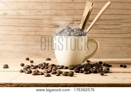 The White Cup Of Coffee And Coffee Beans Seed With Broen Sugar And Wooden Spoon On Wooden Table