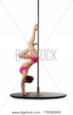 Slim girl in pink bikini posing by the pylon doing handstand isolated studio shot