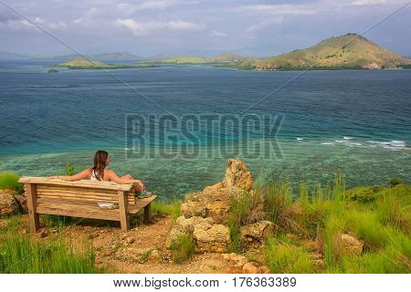 Young Woman Sitting On A Bench At The Viewpoint On Kanawa Island In Flores Sea, Nusa Tenggara, Indon