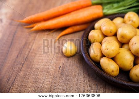 Potatoes in plate. Carrot and raw new potato. Fresh natural vegetables. Organic bio food on rustic wooden table.