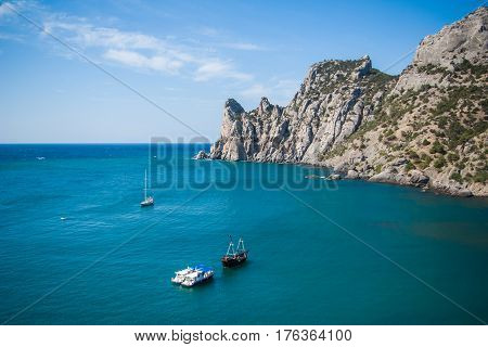 View of the Bay, cliffs, ships and yachts on the waves of the blue sea. Rocky Cove with calm water in foreground and mountains and cliffs in the background.