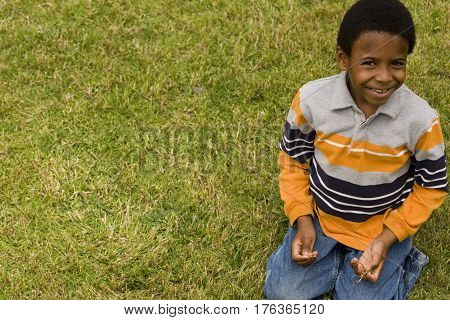 Cute little boy sitting on the grass outside.
