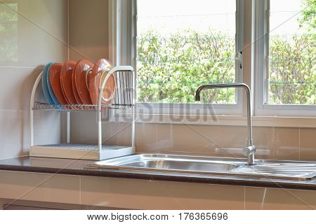 Colorfull Plates On Shelf Next To Sink On Black Marble Top With Natural Light
