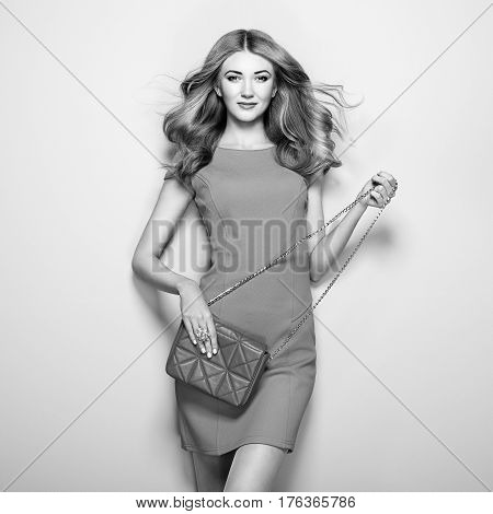 Black and white photo of young woman in elegant dress. Girl posing on a white background. Jewelry and hairstyle. Girl with handbag. Fashion photo