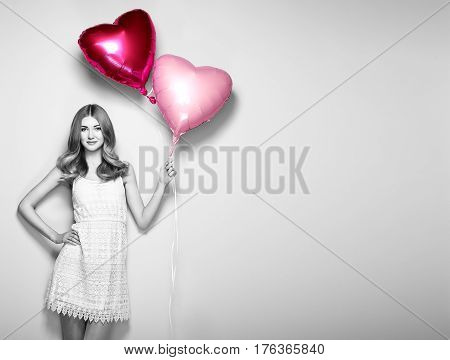 Beautiful young woman with heart shape air balloon on white background. Woman on Valentine's Day. Symbol of love. Black and white photo