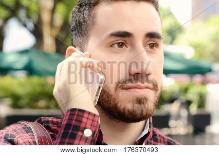 Portrait of young latin man talking on the phone. Outdoors. Urban scene.