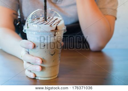 Woman Hand On Iced Milk Coffee Drink stock photo