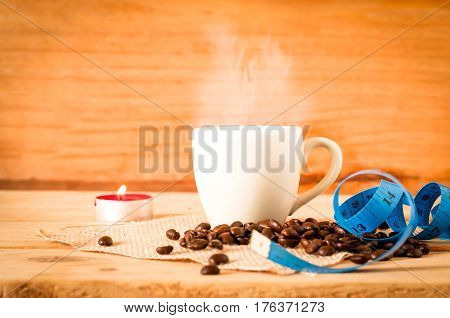 The Hot Coffee In The White Cup With Blue Measuring Tape On Wooden Table And Coffee Bean Seed. Healt