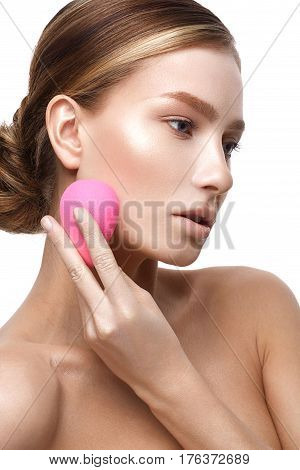 Young girl with a healthy skin and Nude makeup. Beautiful model on cosmetic procedures with a sponge to apply foundation. The beauty of the face.