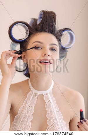 Woman in hair curlers applying mascara indoors at home. Portrait of brunette girl in sexy lacy lingerie holding make-up accessorie and looking at camera like in the mirror.