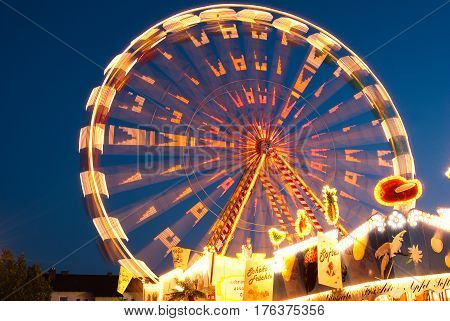Neuoetting,Germany- June 13,2009 : A ferris wheel food stalls at a local fair shines bright  against the evening sky with its lights causing streaks in this long exposure during a local fair