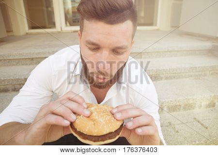 Portrait of young man freelancer having a great desire to eat hamburger. Man in white shirt keeping hamburger in front of him. Toned image.