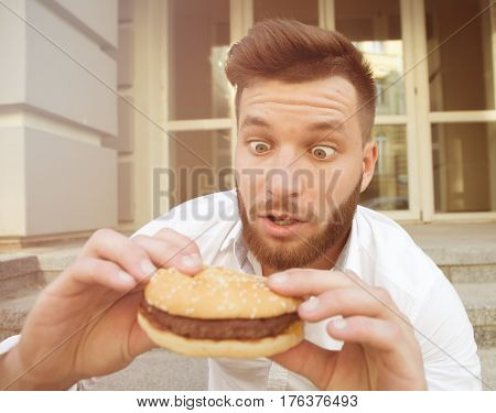 Handsome young man dreaming of tasting delicious cheeseburger very much. Surprised man looking at it with excitement. Toned image.