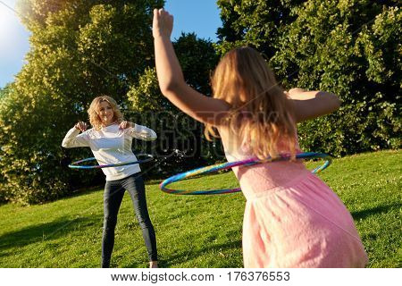 Happy mother and little daughter playing with hula hoops while enjoying a day in a park together on a sunny summer day