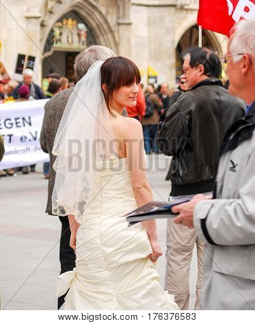 Munich,Germany-April 10,2010: A woman dressed in a bridal gown stands in front of a politcal rally at Marienplatz Square in MunichGermany on a warm spring day