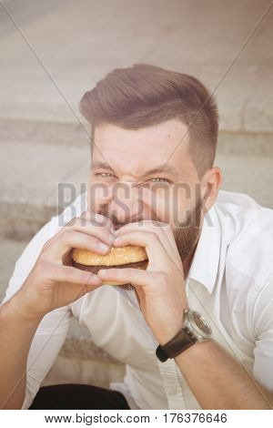 City hipster businessman eating hamburger. Close-up portrait of hungry man having a snack during his break after hard work. Toned image.