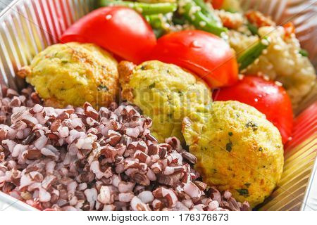 Healthy food delivery closeup diet concept. Take away of fitness meal. Weight loss lunch in foil boxes. Falafel with brown rice and vegetables on white wood