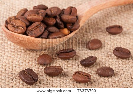 Coffee beans in a wooden spoon on sackcloth.