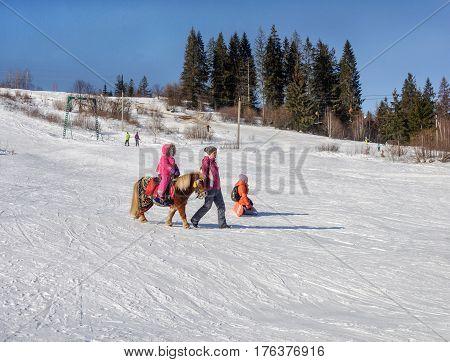 Slavske Ukraine - January 30 2017: Ski resort Slavske in Carpathians. Little girl riding pony on mountain slope. Sunny winter day.