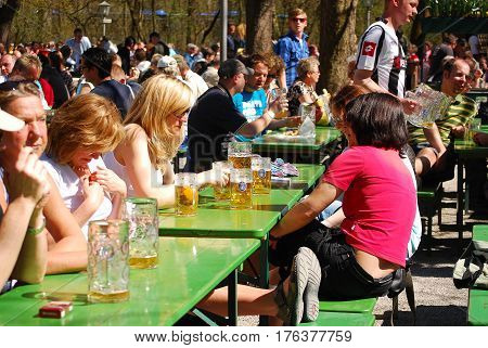 Munich,Germany- April 2,2011 :People sit in a beergarden in a park enjoying the sunny weather