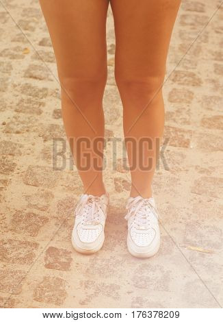 Close-up picture of attractive woman's legs. Beautiful slender female legs in white jogging shoes. Toned image.