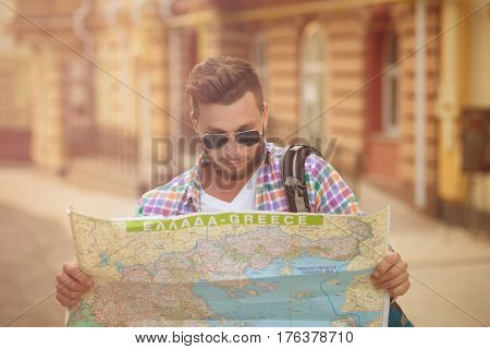 Young hipster man with map outdoors. Serious man with backpack going to find interesting sightseeings in the city. Toned image.