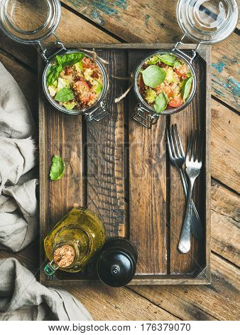Homemade healthy jar quinoa salad with cherry and sun-dried tomatoes, avocado, basil in wooden box over rustic background, top view, copy space. Detox, dieting, vegan, vegetarian, clean eating concept