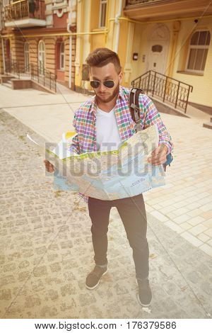 Tourist examining the map. Handsome young bearded man carrying backpack and examining map while walking in the city centre. Toned image.