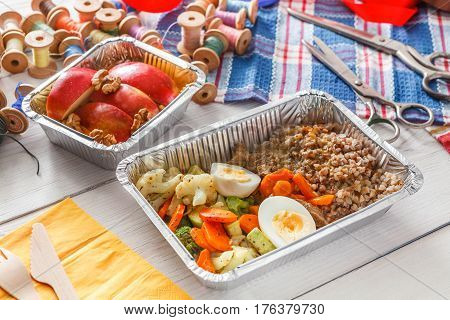 lunch box healthy food delivery for dressmaker. Closeup shot of foil container with diet meal for fashion designer at workplace. Healthy nutrition with fruits, vegetables and proteins