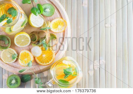 Detox fruit water on wooden table. Fresh homemade lemonade with mint. Summer refreshing citrus water in a mason jar on a bamboo table. Summer homemade cocktail with lemon orange kiwi.
