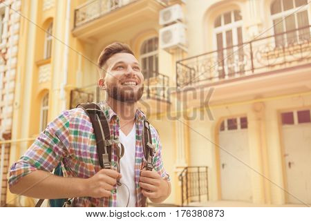 Close-up portrait of happy young hipster man travelling with backpack. Beardeed man walking in the city and enjoying his time. Toned image.