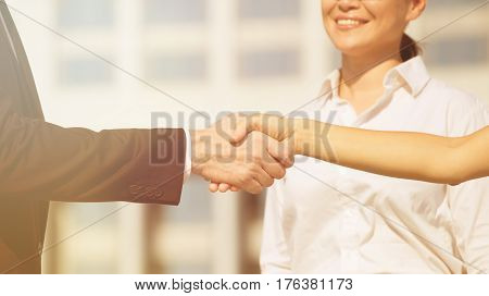 Handshake with businesswoman at backdrop showing business partnership. Man and woman have singed lucrative contract. Toned image.