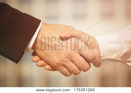 Business handshake on bright background. Photo of handshake of business partners after signing promising contract. Toned image.