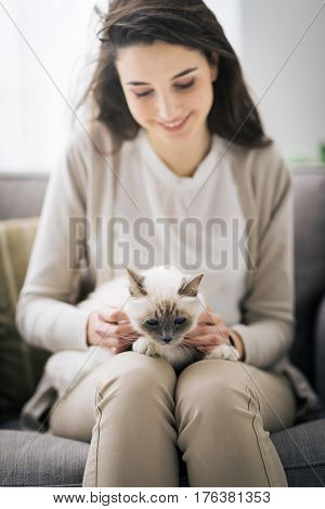 Young smiling woman sitting and cuddling her beautiful birman cat pet care concept
