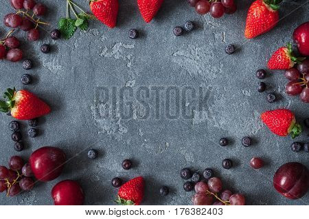 Fruit frame with strawberries blueberries plums grapes on grunge background. Fruit background. Flat lay top view
